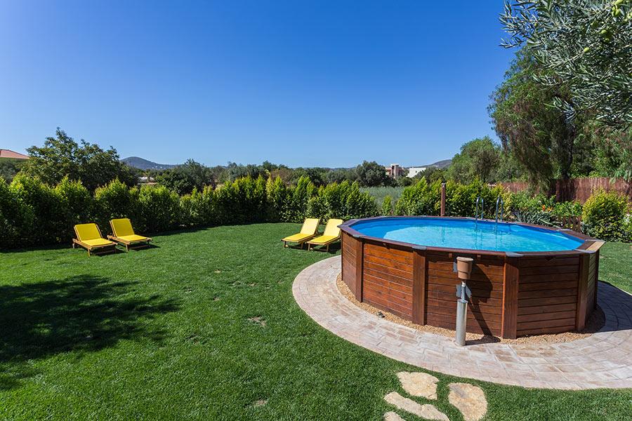 Giardino con piscina in legno e sdraia.