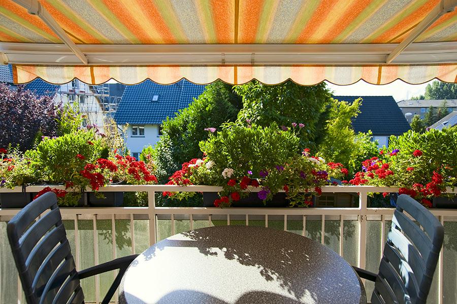 Vista di un balcone da l'interno con tende parasole e tavolo rotondo.