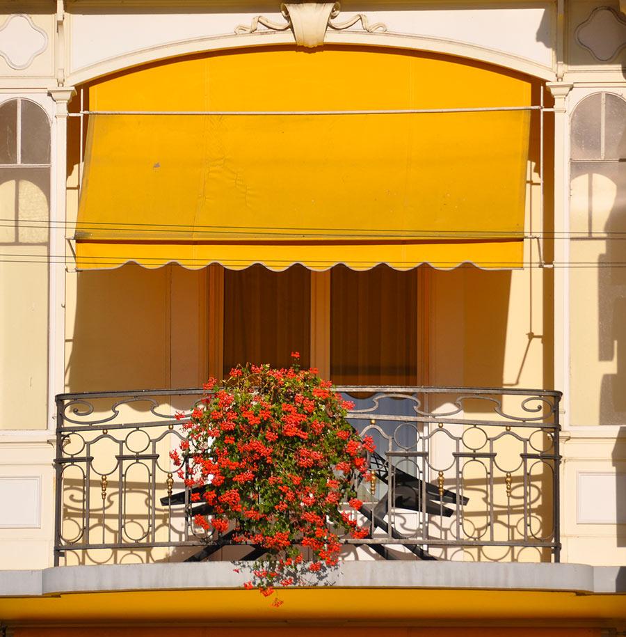 Balcone con tende da sole a caduto e fiori rosse.