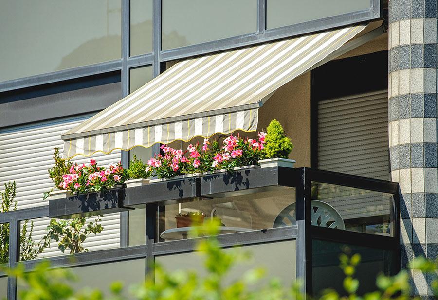 Un bel balcone con tende a strisce e vasi con fiori.