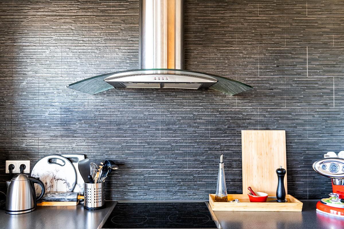 Bellissima piano cottura con cappa cucina moderna in inox e vetro.