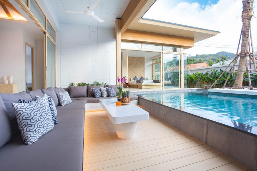 Terrazzo con grande divano e piscina seminterrata.