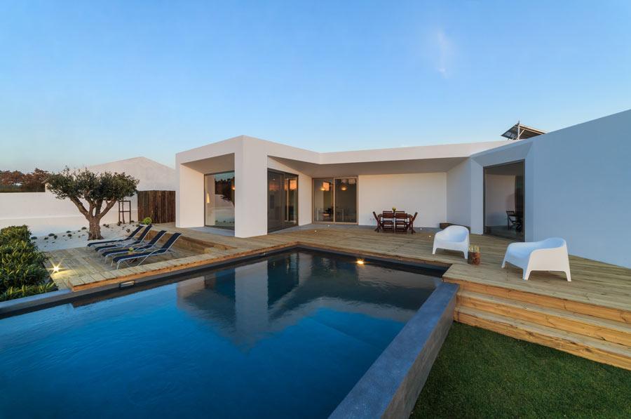Casa moderna con piscina seminterrata con soppalco in legno.