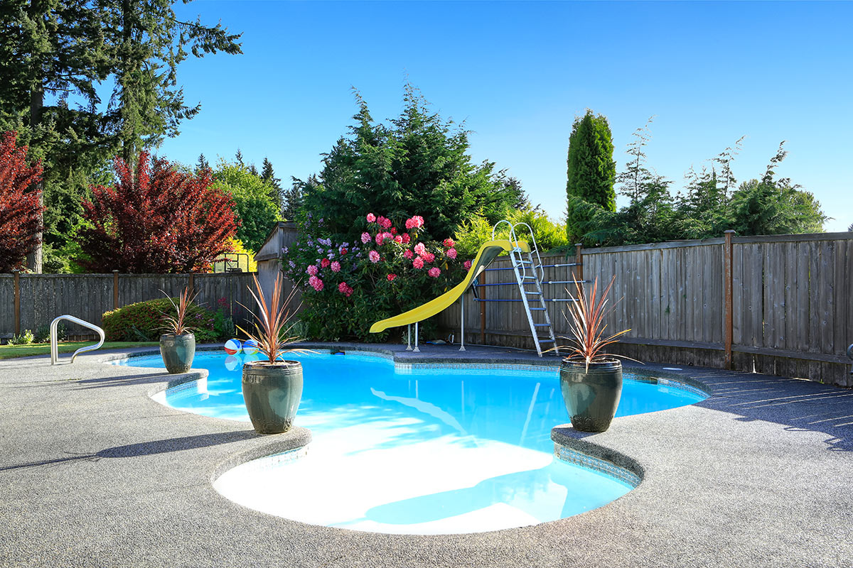 Bellissima piscina interrata a forma libera con scivolo, decorata con vasi di fiori.