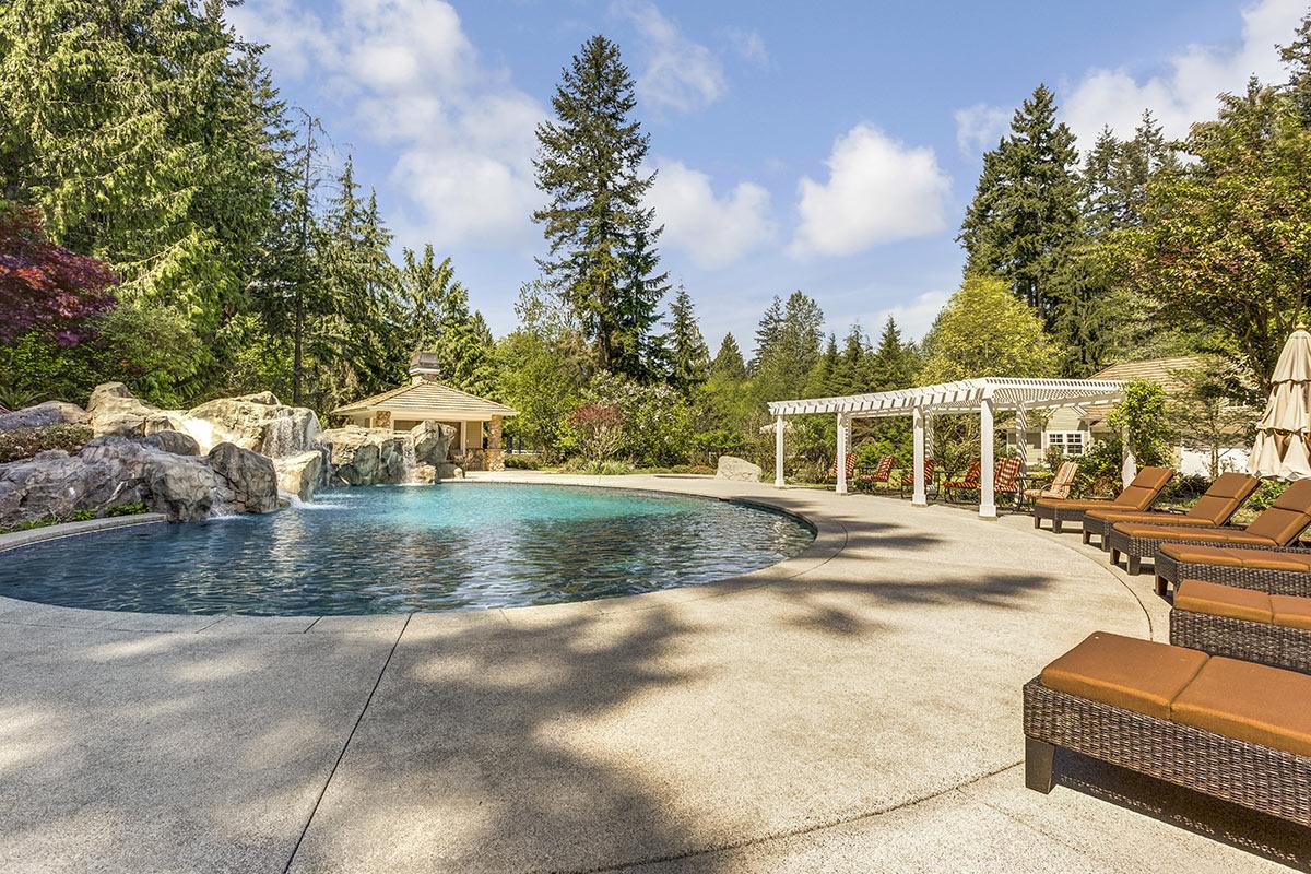 Bella piscina rotonda interrata con pietre e cascata.