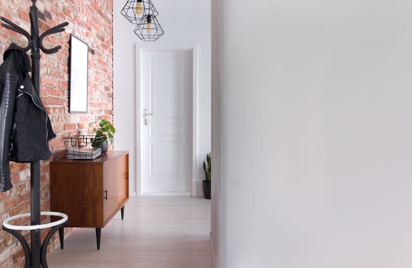 Ingresso di casa con una parete in mattoni rossi, perfetto per un ingresso stile vintage.