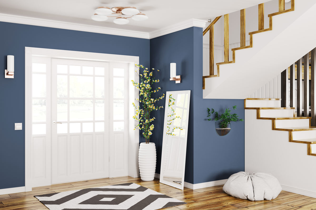 Ingresso di casa accogliente e luminosa con porta bianca e parete blu.