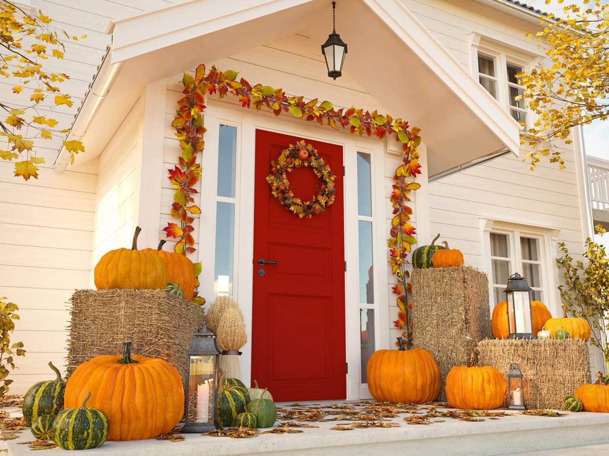 Bellissimo ingresso di casa addobbato per l'autunno con foglie e zucche.