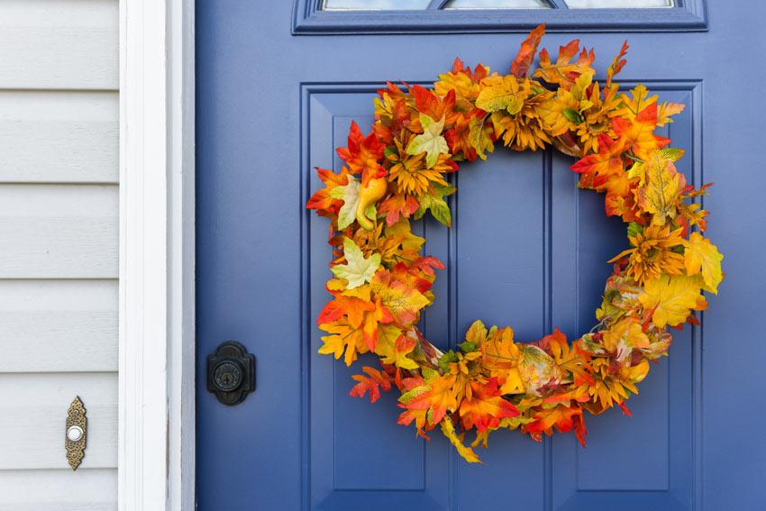 ghirlanda dietro porta realizzato con foglie autunnali.